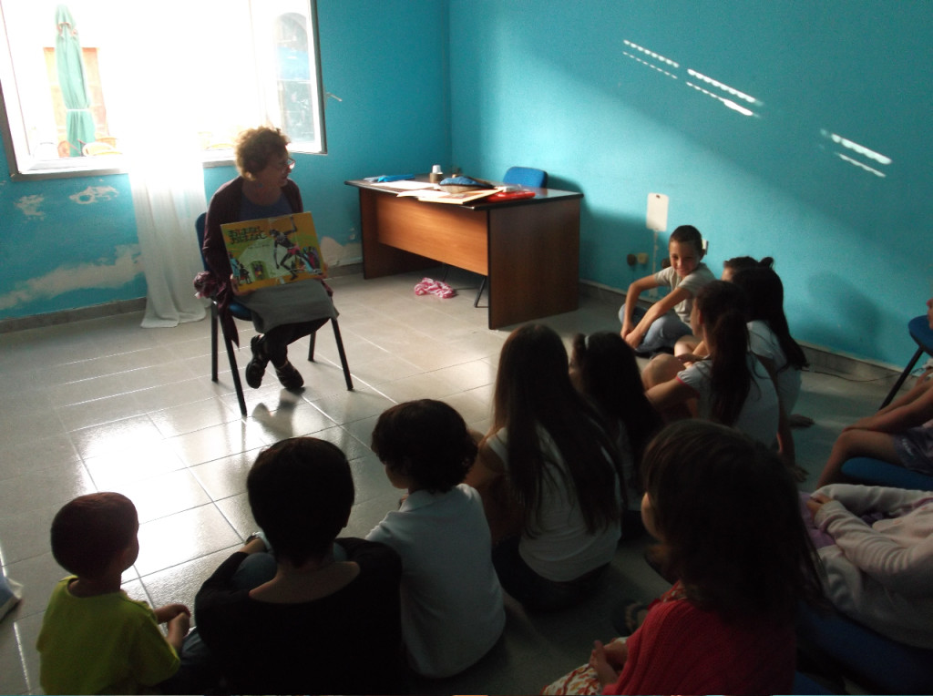 Campers listen to Mariella Bertelli read a story at Camp Lampedusa