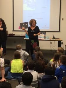 Mariella Bertelli, coordonnatrice de l'exposition Livres sans paroles d'IBBY au Canada, avec des enfants lors de l'exposition à la bibliothèque publique de Winnipeg.