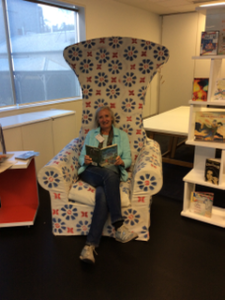 Catherine Mitchell taking a moment in the famed Margaret Mahy chair, which does loom large in the Parnell office of the National Library of New Zealand. Comfy! Photo courtesy of Catherine Mitchell.